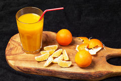 Several mature citrus and a glass of juice on a wooden table on a blackboard - mandarins.  Stock Photos