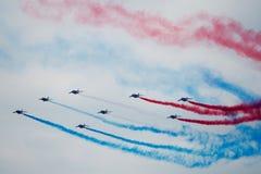 Several military aircraft symmetrically perform aerobatics stock images