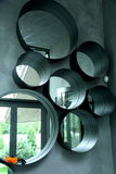Several mirrors. Several round mirrors on the grey wall Royalty Free Stock Photos