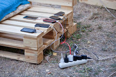 Several mobile phones charging at wooden pallet.  Stock Image