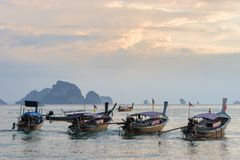 Moored thai traditional long-tail boats in the sea water near the shore in the evening on Ao nang beach in Krabi province royalty free stock image