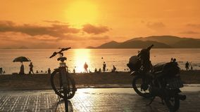 Several motorcycles stand in the parking lot on the embankment of Nha Trang. Vietnam. Evening time and sunset. Several motorcycles stand in the parking lot on