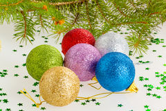 Several multicolored Christmas balls under the tree Stock Image