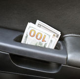 Several notes of US dollars and are folded in half in the door handle of the car. The money in the car.  Stock Photos