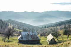 Several old houses on a background of mountains. Horizontal fame stock images