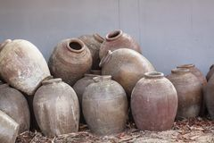 Several old jars were placed on the floor had been used in fermented foods. Several old jars are placed on the ground had been used in the fermentation of food Stock Photo