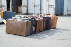 Several old suitcases clothes are on asphalt. Royalty Free Stock Photography