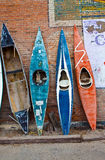 Leaning against the wall-background. Several old time rustic weathered kayaks leaning against a red brick wall in a Colorado mountain town Stock Photo