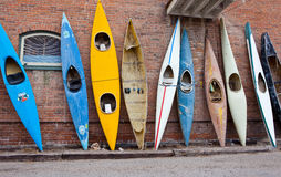 Many old time vintage kayaks stacked against the wall. Several old time rustic weathered kayaks stacked against a brick wall Stock Photos