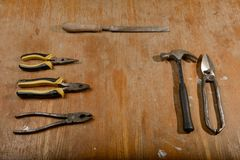Several old tools lie on a wooden table. Several old tools lie on a dirty wooden table stock images