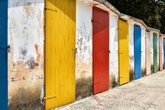 Several old wooden colorful doors on shabby light wall backgroun royalty free stock photo