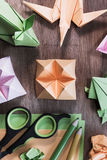 Several origami figures on wooden table. Origami figurines - flower, swallow, rabbit and frog with some colored paper, scissors and pencils - high angle view Stock Photos