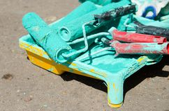 Several paint rollers covered with green paint are in the tray.  royalty free stock image