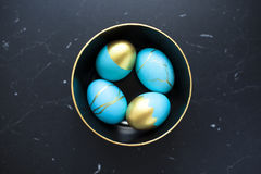 Several painted eggs on a plate with a gold border. A few painted eggs on a plate with a gold frame on a marble surface Royalty Free Stock Images