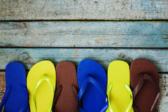 Several pairs of multi-colored rubber flip-flops exhibited in a Stock Photo