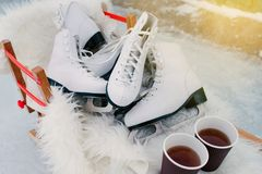 Free Several Pairs Of Ice Skates With 2 Cups Of Coffie Standing On The Wooden Sled. Stock Image - 138360401