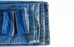 Several pants of shabby jeans on white background. A few shabby trousers stacked on top of each other Stock Photo