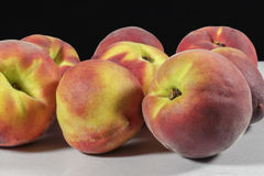 Several peaches on clear and rough surface and black background Royalty Free Stock Image