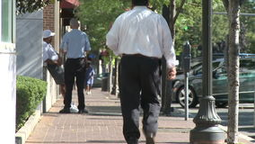 Several pedestrians on quiet sidewalk (2 of 3). A view or scene from around town stock footage
