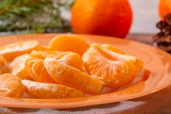 Several peeled tangerine slices on an orange plate with tree branches and a cone-a traditional Christmas and new year`s. Composition in Russia stock photo