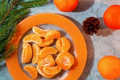 Several peeled tangerine slices on an orange plate with tree branches and a cone-a traditional Christmas and new year`s. Composition in Russia royalty free stock photos