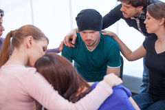 Several people comforting young man on background. Royalty Free Stock Photos