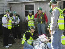 Several people helping the injured person close up image. This is horizontal image with sceene of emergency cituation. Several people  are wearing bright yellow Stock Photography