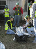 Several people helping the injured person. This is vertical image with sceene of emergency cituation. Several people  are wearing bright yellow safety vest Royalty Free Stock Photos