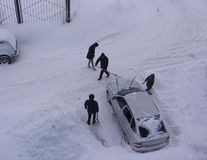 Several people dig up a stuck car in the snow in the Parking lot of the snow stock photos