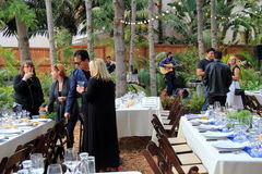 Several people standing near tables set for farm to table benefit dinner, Encinitas, California, 2016. Beautiful detail in tables set for food festival, with Royalty Free Stock Images