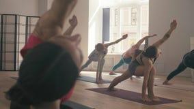 Several people studying yoga in the studio. 4K. Trikonasana stock footage