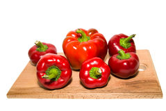 Several  peppers on a wooden cutting board. Royalty Free Stock Photo