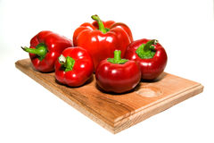 Several  peppers on a wooden cutting board. Royalty Free Stock Photos