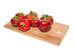 Several  peppers on a wooden cutting board. Royalty Free Stock Images