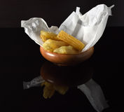 Several pieces of fried yucca in a wooden bowl on a reflective black surface Stock Photo