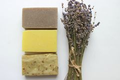 Several pieces of handmade soap and a bouquet of lavender flowers on a white background stock image