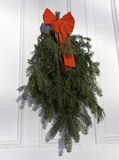 Pine and fir boughs on door with red ribbon Stock Image