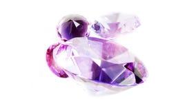 Several pink shiny diamonds on white table Royalty Free Stock Photos