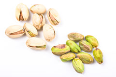 Several pistachio nuts naked and in shell close up Royalty Free Stock Photos