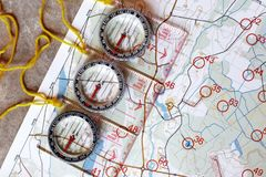 Several plastic transparent compasses. With ruler for orienteering or rogaining sport on color topographical map background. Compass shows north direction Royalty Free Stock Photo