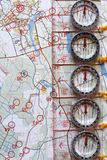 Several plastic transparent compasses. With ruler for orienteering or rogaining sport on color topographical map background. Compass shows north direction Stock Photos