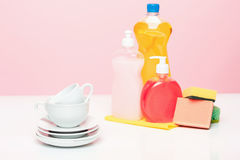 Several plates, a kitchen sponges and a plastic bottles with natural dishwashing liquid soap in use for hand dishwashing Royalty Free Stock Image