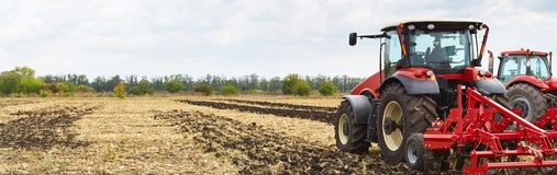 Several powerful tractors work in the field stock image