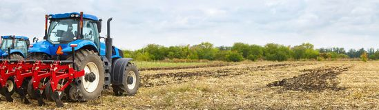 Several powerful tractors work in the field stock photo