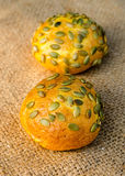 Several pumpkin buns with pumpkin seeds on burlap Royalty Free Stock Photography