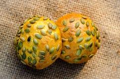 Several pumpkin buns with pumpkin seeds on burlap Stock Photo