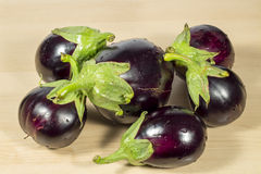 Several purple eggplants on wooden table, seen from top Stock Photos