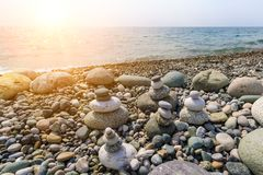 Several pyramids stacked of pebbles on the beach at sunset Stock Photography