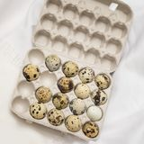 Several Quail eggs in open carton package, rustic linen napkin. Flat lay, top view. Concept for Easter, spring, organic Stock Photos
