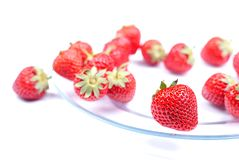 Several randomly distributed strawberries on a transparent plate Stock Image